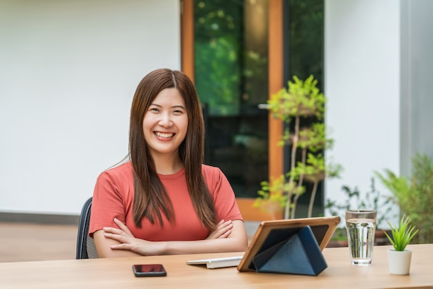 自宅で仕事にテクノロジータブレットを使用してアジアのビジネス女性の肖像画