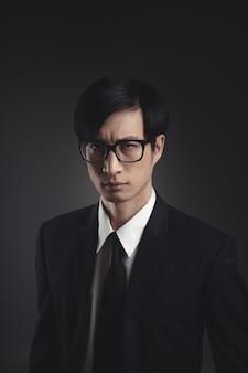 Портрет азиатского бизнесмена в черном костюме на черном