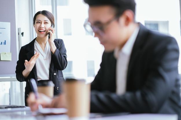 彼女のパートナーを呼び出すアジアの実業家の肖像画