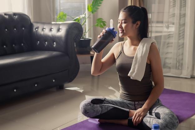 自宅でのトレーニングの後に休んでいるアジアの魅力的なアクティブな女性のポートレート