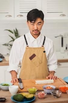 대나무 매트와 초밥 재료로 카메라 초밥 준비를보고 아시아 요리사의 초상화
