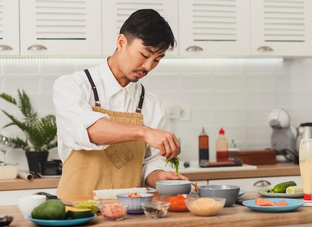 대나무 매트와 초밥 재료로 아시아 요리사 초밥 준비의 초상화