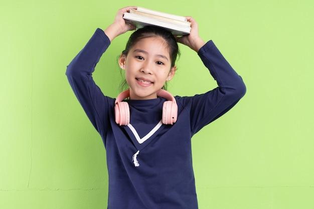 녹색 bkacground에 책을 들고 아시아 아이의 초상화