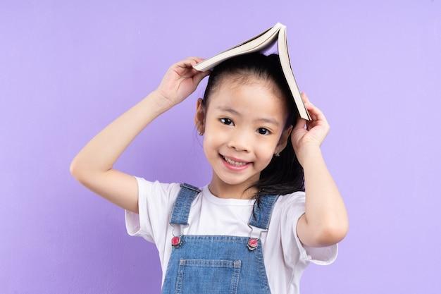 보라색 배경에 책을 들고 아시아 어린이의 초상화