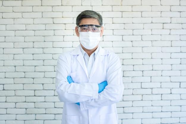 アジアの長老の医師または研究者の肖像画は、白衣、透明な眼鏡、立っているフェイスマスク、白いレンガの背景と交差した腕を着用しています。