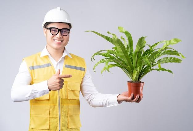 Портрет азиатского инженера, держащего в руке горшечные растения