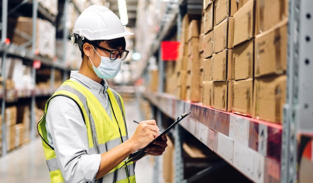 保護マスクを身に着けているコロナウイルスの検疫でヘルメットをかぶったアジアのエンジニアの男性の肖像画注文の詳細倉庫の商品の背景を持つ棚の商品や消耗品をチェック