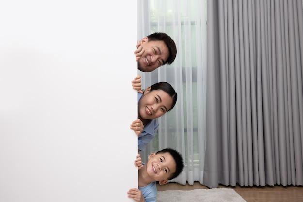 Портрет азиатской семьи с сыном, выглядывающим за пустой белой доской и фоном гостиной дома