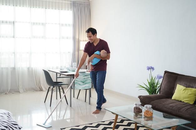 그의 유아 아기를 운반하는 동안 빗자루를 사용하여 바닥을 청소 아시아 아버지의 초상화