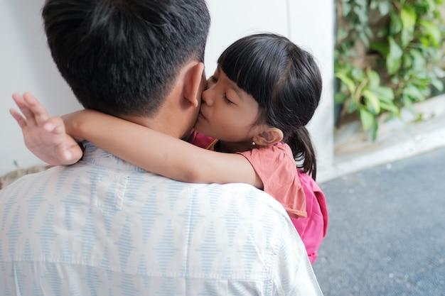 アジアの父の肖像画は、朝学校に行く前に彼の娘を抱きしめます