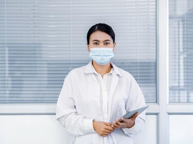 デジタルタブレットを保持している白い白衣で医療フェイスマスクを身に着けているアジアの女性医師の肖像画 Premium写真
