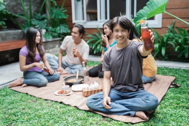 뒷마당에서 먹고 마시는 동안 재미 아시아 친구의 초상화