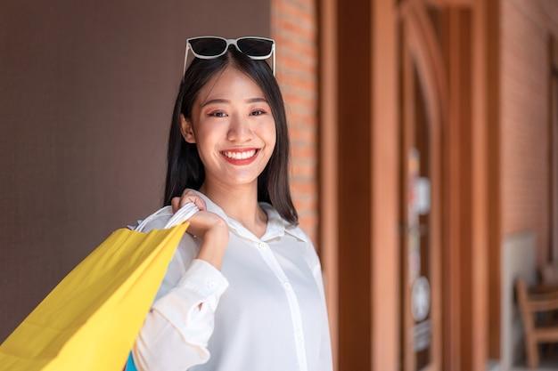 リラックスした表情で買い物を楽しんで買い物袋を持って笑顔アジアの女の子の肖像