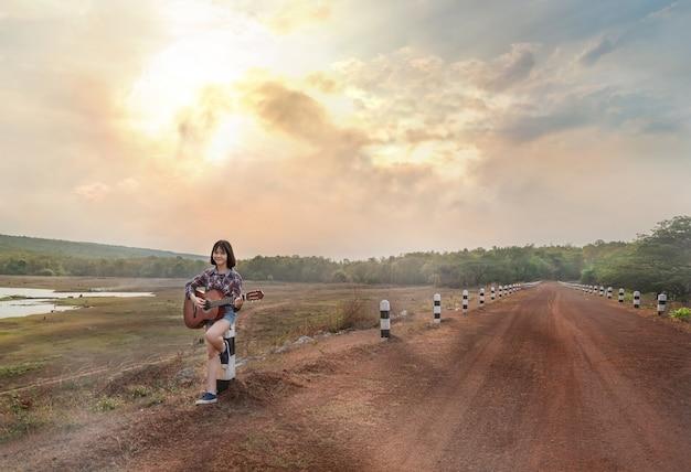Портрет азиатской девушки с гитарой