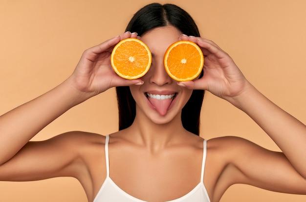 베이지 색에 고립 된 흰색 속옷에 오렌지 반쪽을 들고 얼굴의 깨끗한 피부를 빛나는 아시아 여자의 초상화