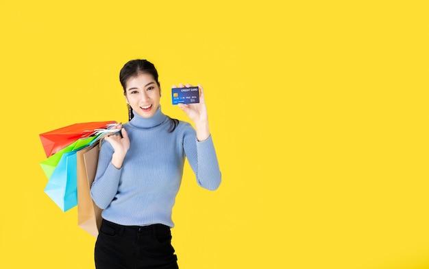 화려한 쇼핑 가방을 들고 신용 카드를 보여 아시아 행복 여성의 초상화