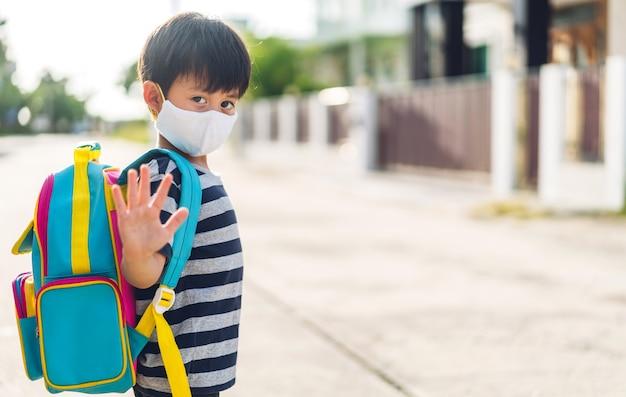 社会的距離の準備ができているコロナウイルスの検疫で保護安全マスクを身に着けているアジアの小さなアジアの少年の肖像画は、バックパックでcovid-19の後に学校に戻ります。学校のコンセプトに戻る