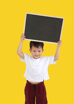 노란색 배경에 격리된 빈 칠판을 들고 있는 아시아 어린 소년의 초상화. 클리핑 패스가 있는 이미지.