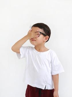 안경을 쓰고 흰색 배경에 격리된 한 손으로 눈을 감고 있는 아시아 어린 소년의 초상화