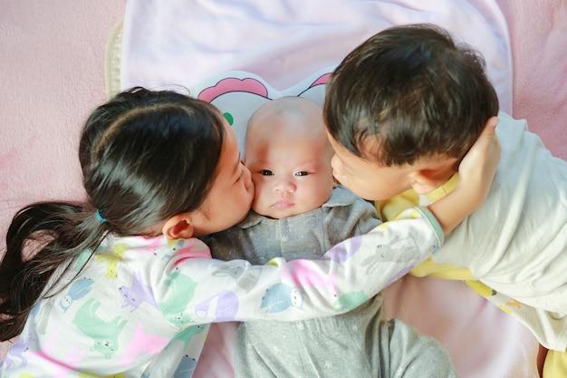 Портрет азиатской маленькой девочки и ее младшего брата, целующих ее новорожденную сестру, лежащую на кровати