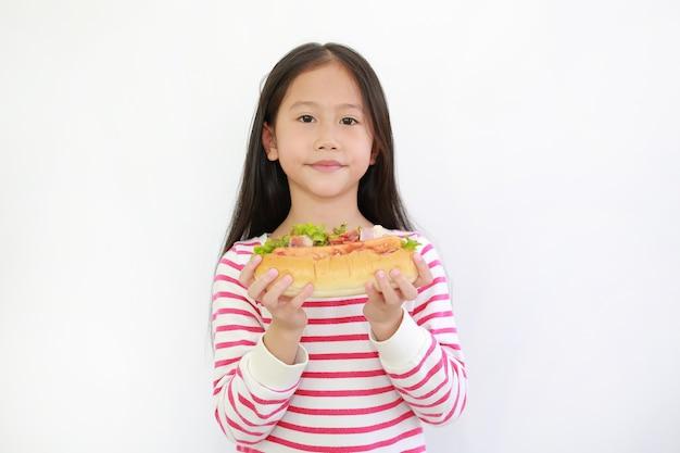 白い背景にあなたのためにホットドッグを保持しているアジアの小さな子供の女の子のポートレート。子供の顔に焦点を当てる
