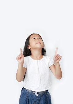 Портрет азиатской девушки маленького ребенка указывая указательный палец 2 вверх и смотря над изолированный