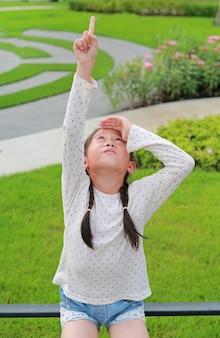 Портрет азиатской маленькой девочки, указывающей указательным пальцем вверх и смотрящей вверх, сидя на заборе в саду