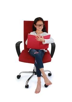 흰색 배경에 격리된 빨간색 패브릭 의자에 앉아 책에 글을 쓰는 아시아 어린 소녀의 초상화. 클리핑 패스가 있는 이미지