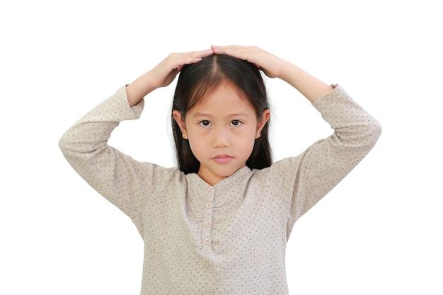 Портрет азиатской маленькой девочки положил руки на голову и смотрит в камеру