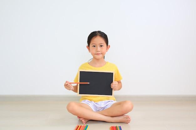 黒板を保持し、ボードの空きスペースに色鉛筆を指して屋内に座っているアジアの少女の肖像画