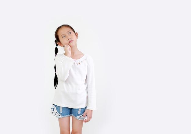 思考表現と白で隔離の見上げるアジアの小さな子供の女の子の肖像画