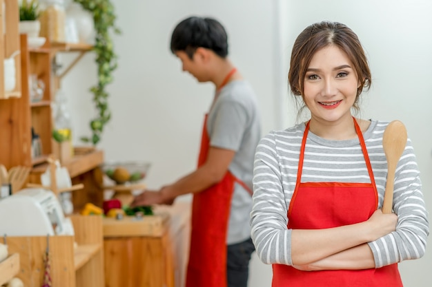 アジアの恋人やキッチンルームでアクションを笑顔で料理のカップルの肖像画