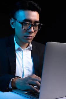 밤에 일하는 아시아 남성 프로그래머의 초상화