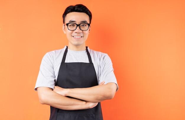 주황색 벽에 포즈 아시아 남성 웨이터의 초상화