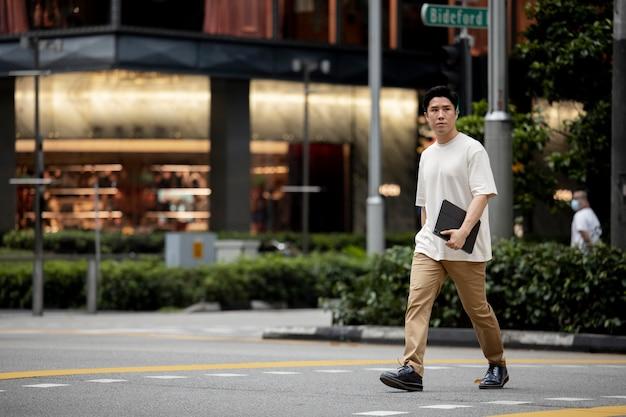 Портрет азиатского мужчины, пересекающего улицу города, держа в руках ноутбук