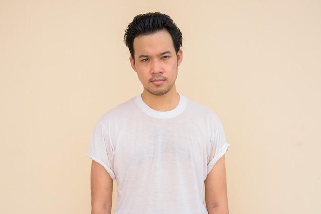 야외에서 평범한 배경에 캐주얼한 흰색 티셔츠를 입은 아시아 남자의 초상화