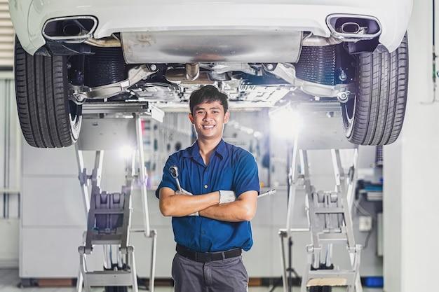 Портрет азиатского механика с ремонтным оборудованием, стоящего под автомобилем