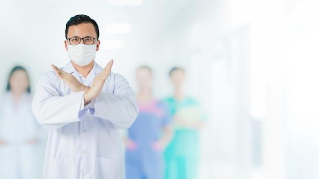 Портрет азиатского медицинского мужского доктора носить маску для предотвращения микробов и стоя и поднимая руку, чтобы показать символ неправды перед его затуманенное сотрудников команды на фоне больницы.