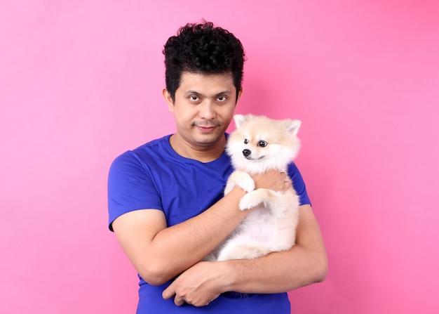 아시아 남자의 초상화는 사랑과 함께 벽에 핑크와 함께 연주 pomeranian 개를 잡아.