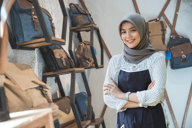 태블릿 자신의 가방 가게 앞에 서 아시아 이슬람 비즈니스 소유자의 초상화