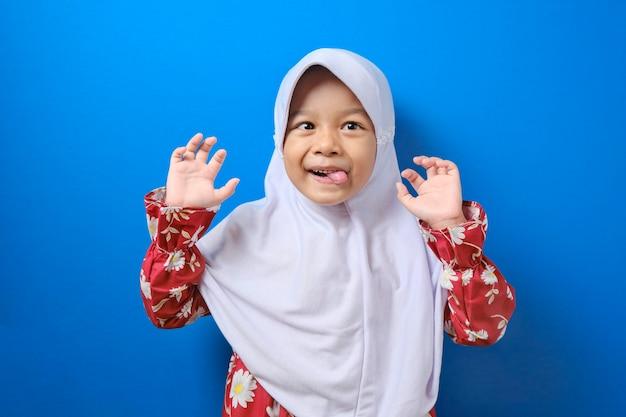 非常に怠惰な不幸な退屈で疲れたジェスチャーを示すヒジャーブを身に着けているアジアのイスラム教徒の少女の肖像画