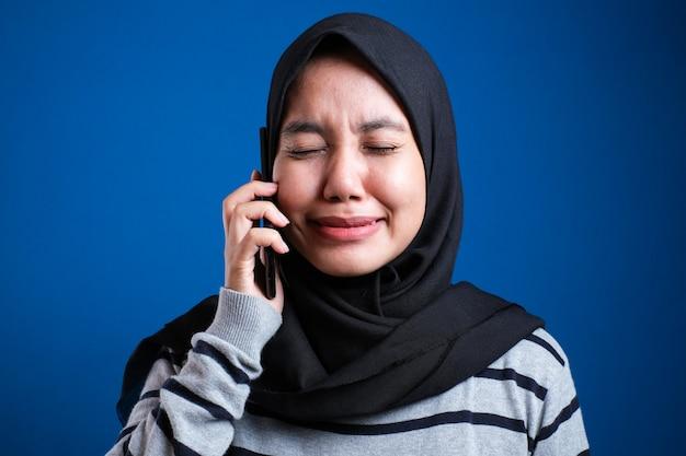 Портрет азиатской мусульманской женщины получает плохие новости по телефону, грустное плачущее выражение. на синем фоне
