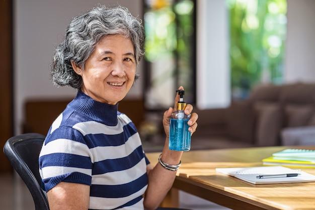 Портрет азиатской пожилой женщины показывает дезинфицирующее средство для рук, накачивая спиртовой гель и стирая