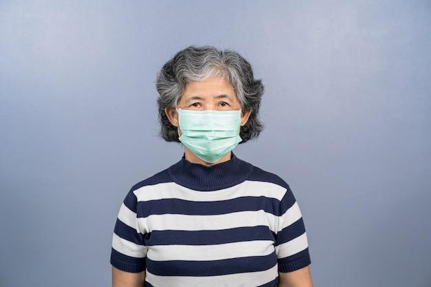 파란색 배경 코로나바이러스에 얼굴 수술용 마스크를 쓴 아시아 노부인의 초상화