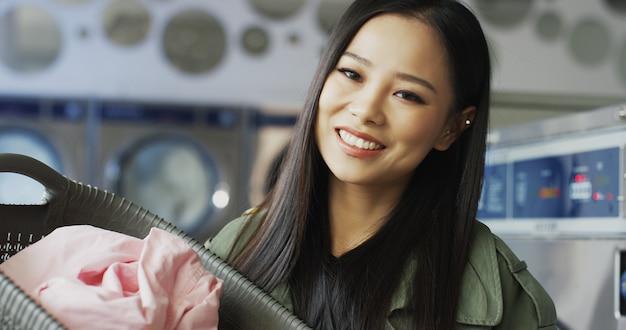 Портрет азиатской милой молодой женщины держа корзину с чистыми одеждами после мыть и усмехаться к камере. закройте вверх красивой стильной девушки с улыбкой в комнате прачечной.