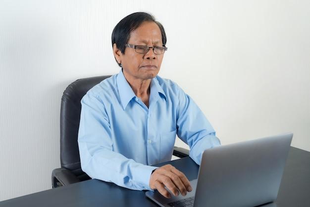 Портрет азиатского старшего мужчины, использующего ноутбук