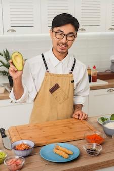 초밥을 만들기 위해 균일한 절단 아보카도를 입은 아시아 웃는 요리사의 초상화