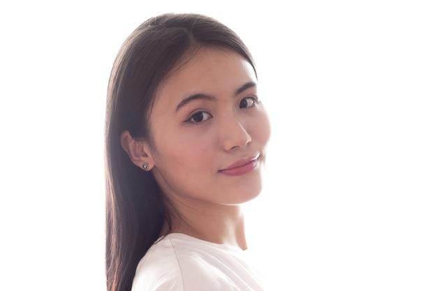 Портрет азиатской усмехаясь женщины на белой предпосылке.