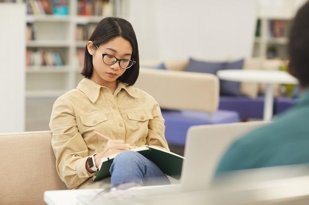 大学図書館で勉強しているアジアの10代の少女の肖像画