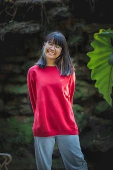 屋外に立っている眼鏡をかけているアジアのティーンエイジャーの肖像画